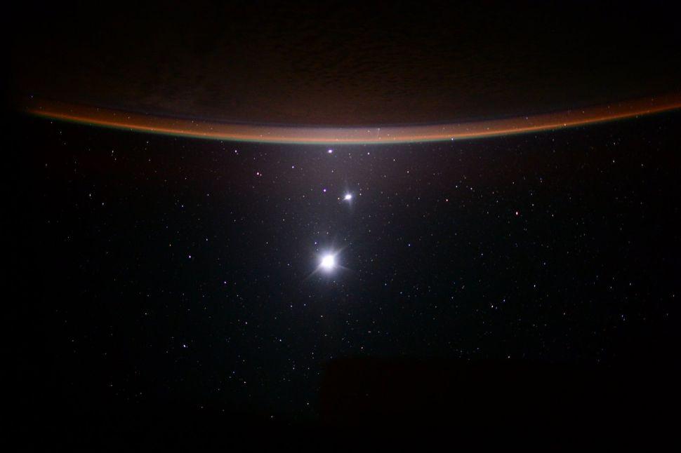 De abajo hacia arriba, los puntos brillantes en esta imagen muestran la luna de la Tierra, Venus y Júpiter. El horizonte curvo en la parte superior es la media luna de la Tierra. El astronauta Scott Kelly capturó esta vista desde la Estación Espacial Internacional en 2015